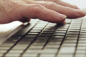 photo illustrant une personne âgée utilisant un clavier d'ordinateur