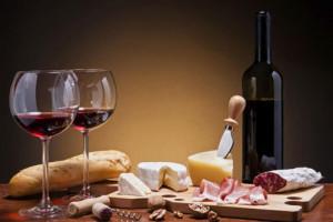 Image de pain, saucisson, fromage et boisson qui ressemble à du vin rouge